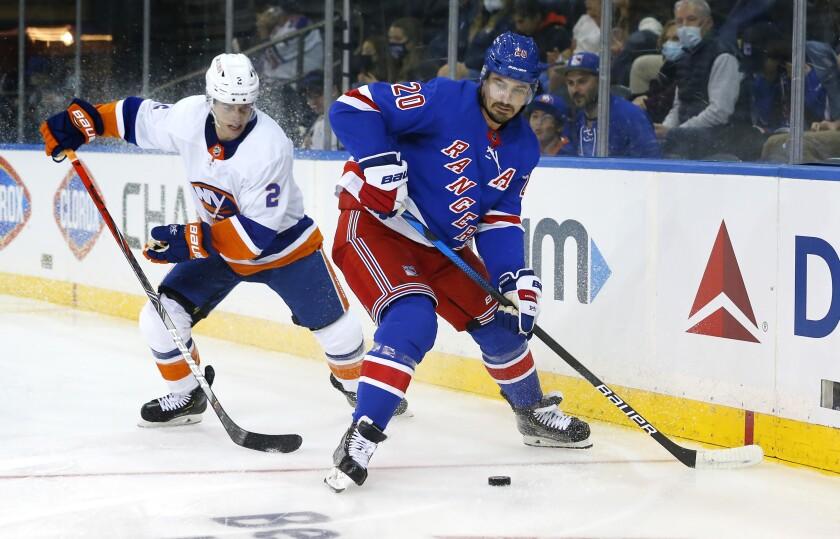 New York Rangers Chris Kreider (20) plays the puck against New York Islanders Thomas Hicky (2) during the second period of a preseason NHL hockey game, Sunday, Sept. 26, 2021, in New York. (AP Photo/Noah K. Murray)