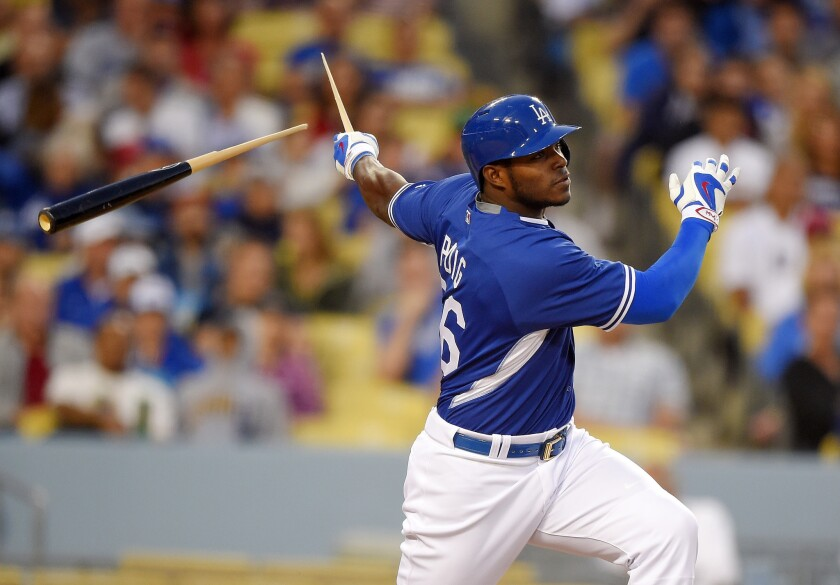 Los Angeles Dodgers' Yasiel Puig breaks his bat as he singles during the fourth inning of a preseason Major League Baseball game against the Los Angeles Angels on Saturday in Los Angeles.