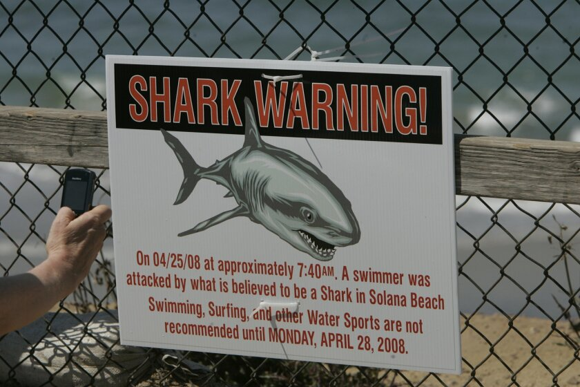 A warning sign was tied to the fence on the outlook overlooking the site of a fatal shark attack at Fletcher Cove in Solana Beach the day after the 2008 attack.