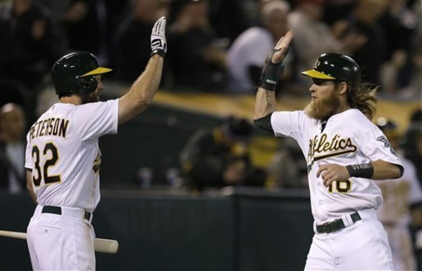 Oakland Athletics' Josh Reddick, right, is congratulated by Shane Peterson (32) after Reddick scored against the Houston Astros in the eighth inning of a baseball game Tuesday, April 16, 2013, in Oakland, Calif. (AP Photo/Ben Margot)