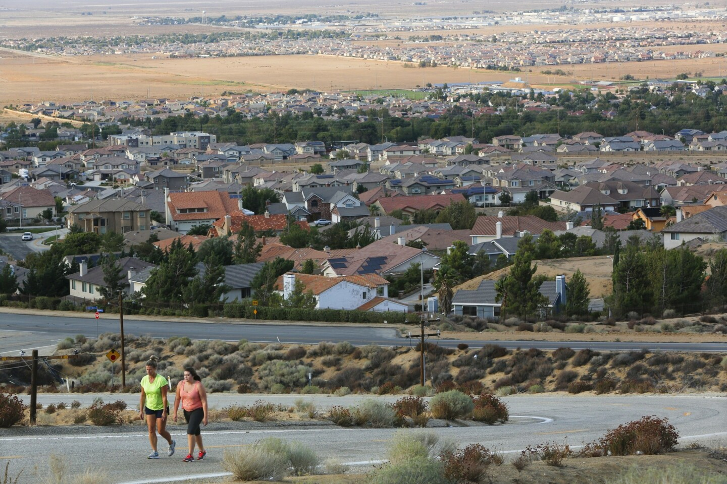 Penny Munz, left, walks with her daughter Stephanie in Palmdale; Lancaster is in the distance. The rift between the two towns has baffled residents, city employees and business interests.