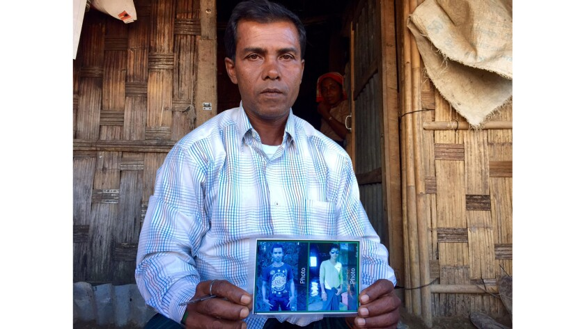 Shafiq Ahmed, 43, in front of his hut in Thet Kae Pyin camp, Myanmar, holds a picture of his sons. The family was chased out of its hometown by Buddhist mobs and government forces.