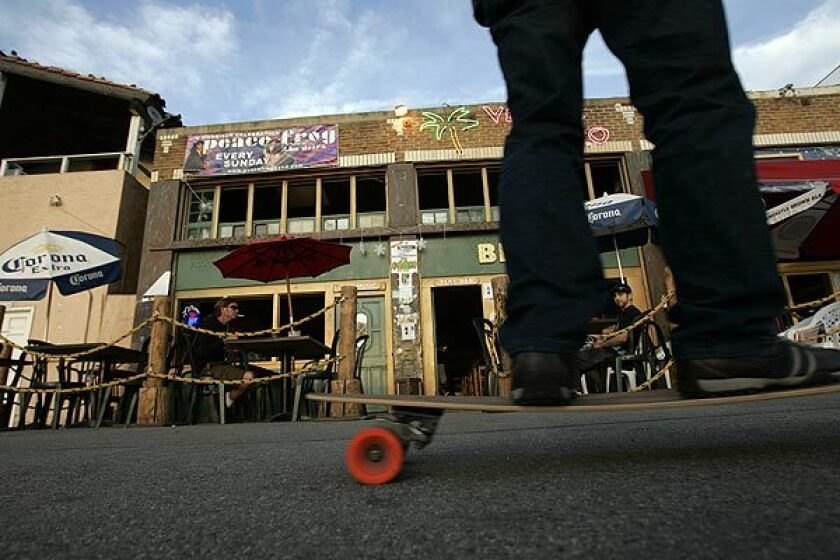 A skateboarder passes diners along Ocean Front Walk near the former Venice West Cafe, L.A.'s headquarters for artists, poets, musicians and other Beat adherents in the 1960s. The city may designate the site a historic-cultural landmark.