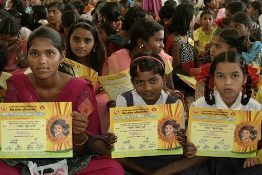 """Girls hold certificates stating their new official names during a renaming ceremony in Satara, India, Saturday, Oct. 22, 2011. Almost 300 Indian girls known officially as """"Unwanted"""" have traded their birth names for a fresh start in life. Given names like """"Nakusa"""" or """"Nakushi"""" _ or """"unwanted"""" in Hindi _ they grew up understanding they were a burden in families that preferred boys in Maharashtra state. (AP Photo)"""