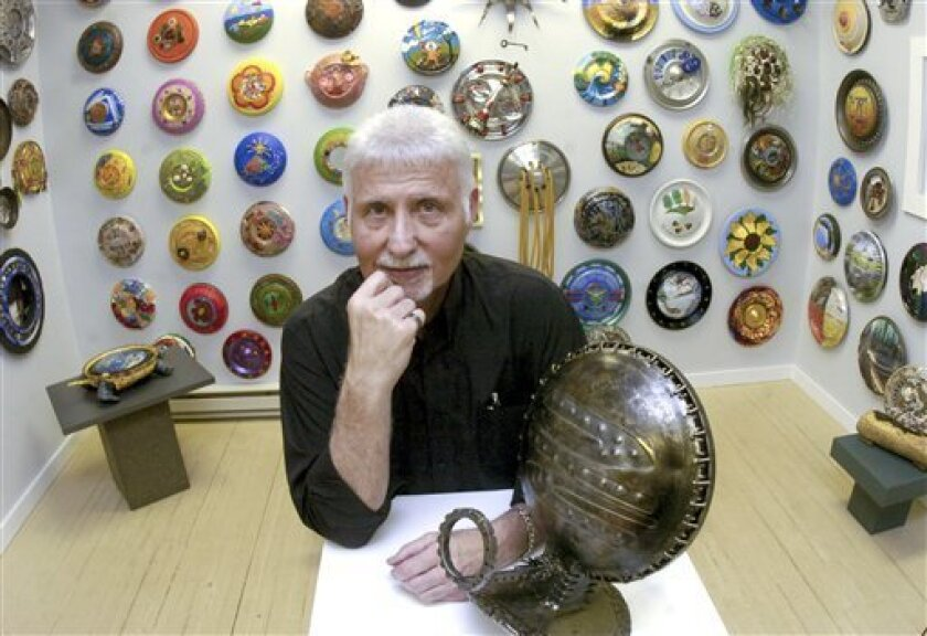 In this photo taken May 24, 2011, Ken Marquis, founder of the Landfillart Project, stands in one of the three areas of his Wilkes-Barre, Pa., art gallery Tuesday, May 24, 2011, among so of the 800 plus hubcaps he has been sent from artist in 52 different countries. When complete the collection with showcase 1,041 hubcaps, which are used in different mediums by artist to give them a second life. (AP Photo/Jimmy May)