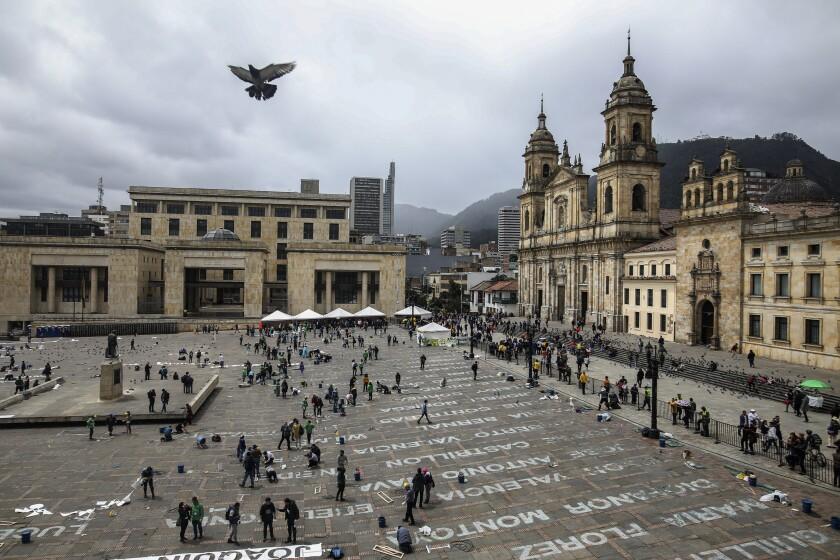 ARCHIVO - Esta fotografía del 10 de junio de 2019 muestra a activistas que han recibido amenazas de muerte mientras escriben los nombres de activistas de izquierda asesinados, como parte de una instalación de la artista colombiana Doris Salcedo en la Plaza Bolívar del centro de Bogotá, Colombia. (AP Foto/Ivan Valencia, Archivo)