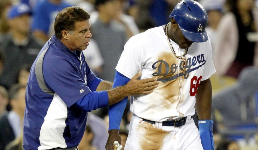 Dodgers right fielder Yasiel Puig (66) plays the game in a do-or-die style, which leds to plenty of check-ups from trainer Stan Conte, left, before, during and after games.