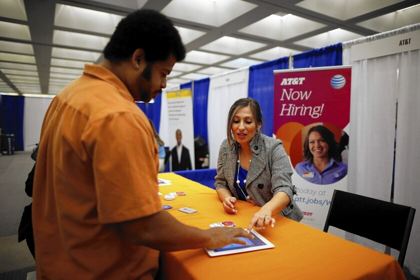 AT&T hiring manager Cathy Zavala (R) talks to Jose Blackman, 38, who was laid off last year and is looking for a job to support his two children, in Los Angeles.