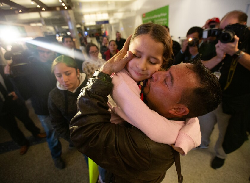 Esvin Fernando Arredondo embraces his daughter, Alison Arredondo, at Los Angeles International Airport