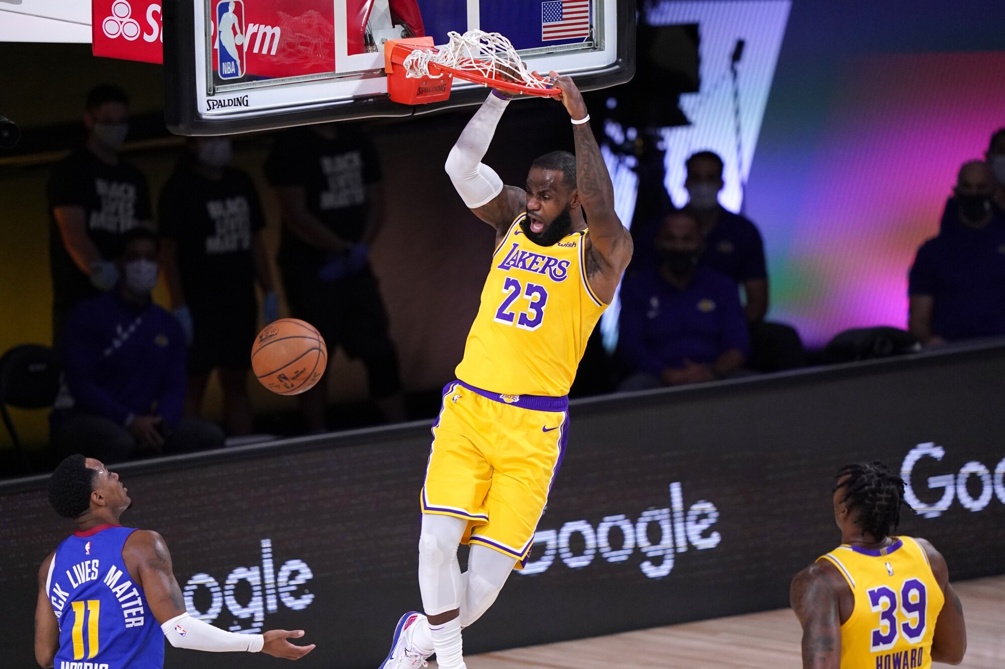 Lakers star LeBron James dunks during the first half against the Denver Nuggets.
