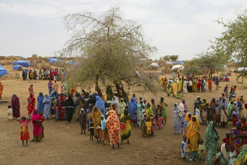 FILE - In this Thursday, July 1, 2004 file photo, Sudanese displaced women gather at the Zam Zam refugee camp just outside the town of El-Fashir in the Darfour region of Sudan, during a visit by U.N. Secretary General Kofi Annan. Sudanese militia leader Ali Kushayb, who is charged with 50 crimes against humanity and war crimes related to the conflict in Darfur, has been arrested more than 13 years after a warrant was issued for him, authorities said Tuesday, June 9, 2020. (AP Photo/Karel Prinsloo, File)