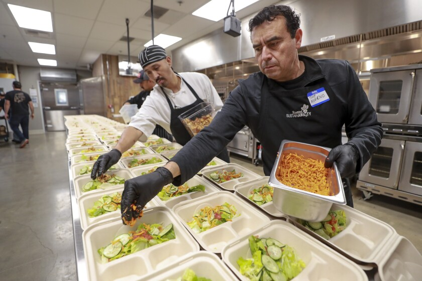 Tony Moreno, right, and Jose Pablo place salad items onto plates as they and other O'side Kitchen Collaborative volunteers, who are kitchen staff workers at various local restaurants, prepare soup and salad dinners for seniors at the Green Oceanside Kitchen on Tuesday.