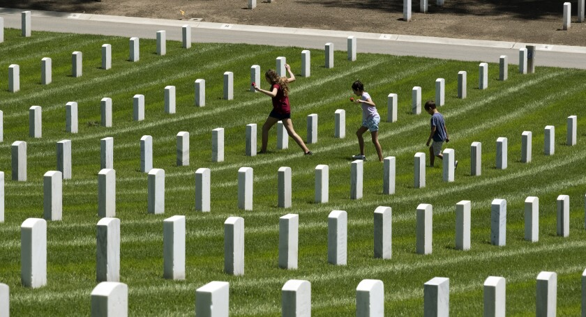 Children place flowers at the graves of fallen soldiers to pay their respects during Memorial Day observances Monday at the Los Angeles National Cemetery.