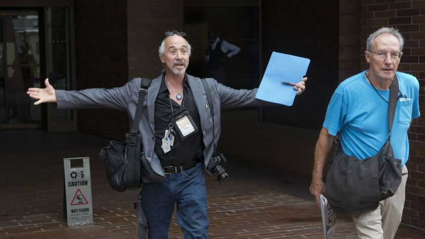 New York Daily News staff photographers Todd Maisel, left, and Andrew Savulich walk out of the newspaper's office Monday after being laid off.