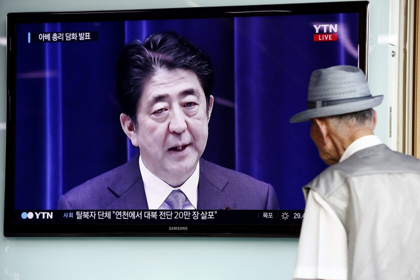 A South Korean man watches at a Seoul train station as Japanese Prime Minister Shinzo Abe speaks in Tokyo on Aug. 14.