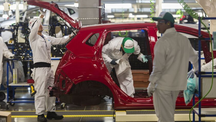 Workers build a vehicle on a Honda Motors factory assembly line in Celaya, Mexico, in 2014.