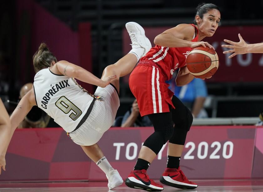 La belga Marjorie Carpreaux (9) pierde el balance mientras la puertorriqueña Michelle González (91) doina el balón en el partido del baloncesto femenino de los Juegos Olímpicos de Tokio, el viernes 30 de julio de 2021, en Saitama. (AP Foto/Eric Gay)