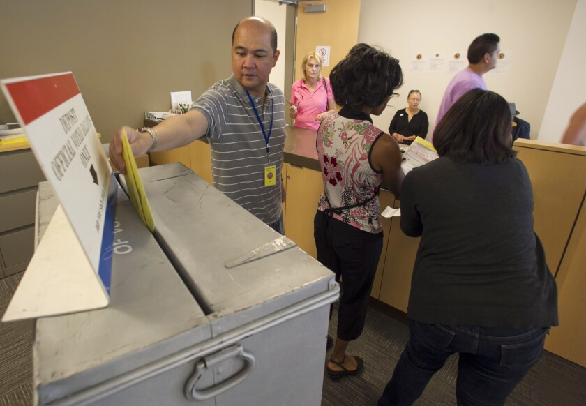 The first day of voting in San Diego County saw several people coming the the Registrar of Voters office in Kearny Mesa to cast their ballots. Registrar ballot worker Michael Nacpil deposits completed ballots after voters completed them and signed their envelopes.