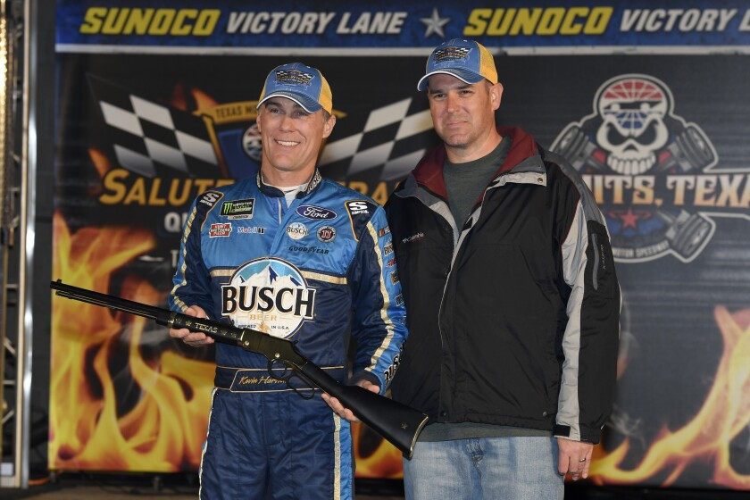 Kevin Harvick, left, poses with local military veteran Joshua Hoscheid, right, in Victory Lane after Harvick won the pole for Saturday's NASCAR Cup Series auto race at Texas Motor Speedway in Fort Worth, Texas, Saturday, Nov. 2, 2019. (AP Photo/Larry Papke)