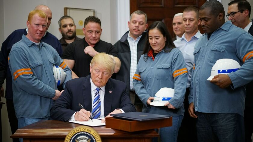 President Trump signs an executive order levying tariffs on imported steel and aluminum at the White House on March 8.