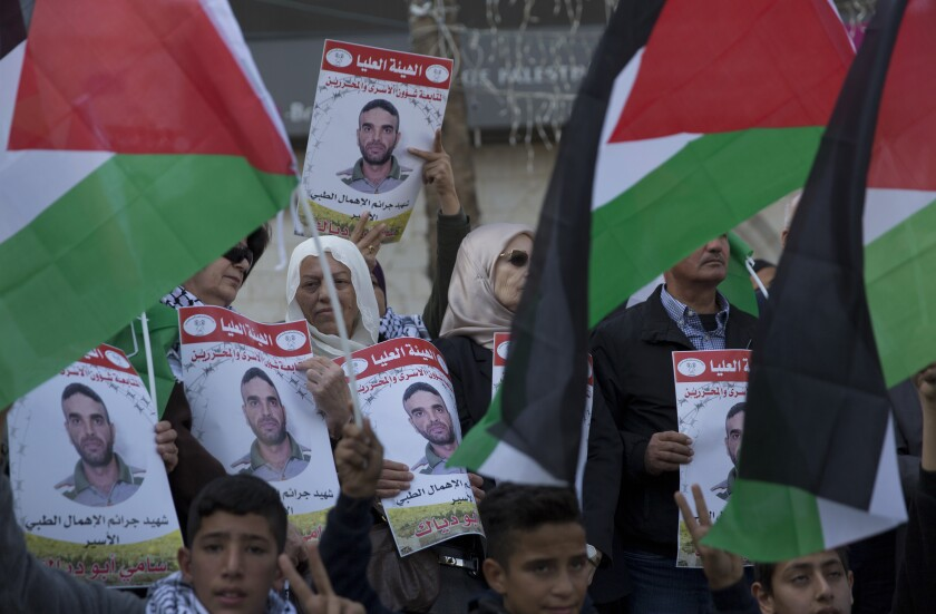 Protesters carry posters with pictures of Sami Abu Diak, a Palestinian prisoner in Israel who died Nov. 26, during a demonstration in the West Bank city of Ramallah.
