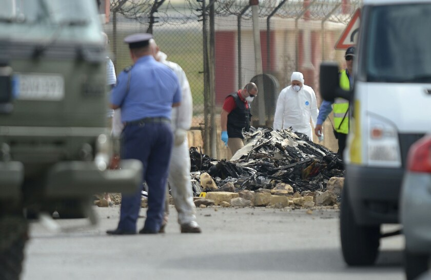 Forensics work on the site of a small plane crash at Malta International Airport on Oct. 24, 2016.