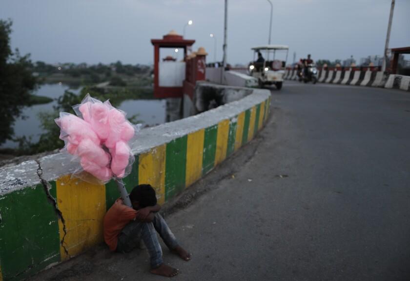 یک فروشنده خیابانی جوان که آب نبات می فروشد ، سرش را روی زانوها گذاشته و کنار جاده نشسته است