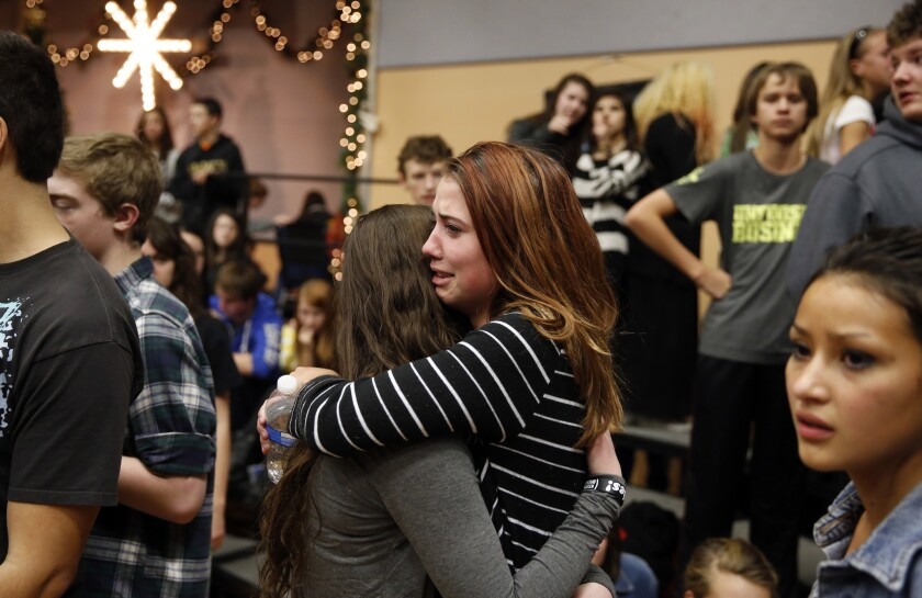 Freshman Allie Zadrow, center right, hugs classmate Liz Reinhardt at a church after a shooting at nearby Arapahoe High School in Centennial, Colo. Students from the school were evacuated to the church.