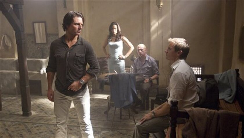 """FILE- In this file image released by Paramount Pictures, Tom Cruise plays Ethan Hunt, left, Paula Patton plays Jane, Simon Pegg plays Benji, and Jeremy Renner plays Brandt, right, in a scene from """"Mission: Impossible - Ghost Protocol."""" (AP Photo/Paramount Pictures, David James, FILE)"""