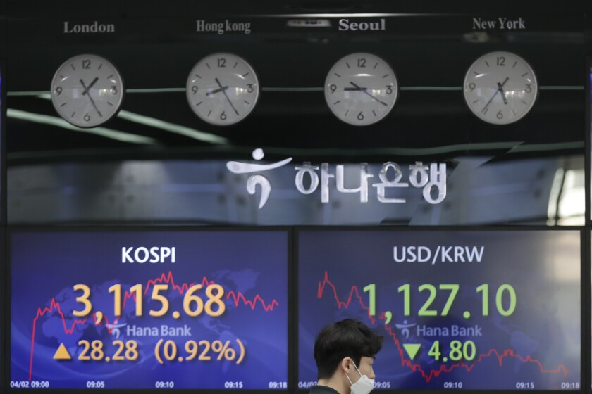 A currency trader walks near the screens showing the Korea Composite Stock Price Index (KOSPI), left, and the foreign exchange rate between U.S. dollar and South Korean won at the foreign exchange dealing room of the KEB Hana Bank headquarters in Seoul, South Korea, Friday, April 2, 2021. Asian shares were higher Friday after a broad rally pushed the S&P 500 past 4,000 points for the first time. (AP Photo/Lee Jin-man)