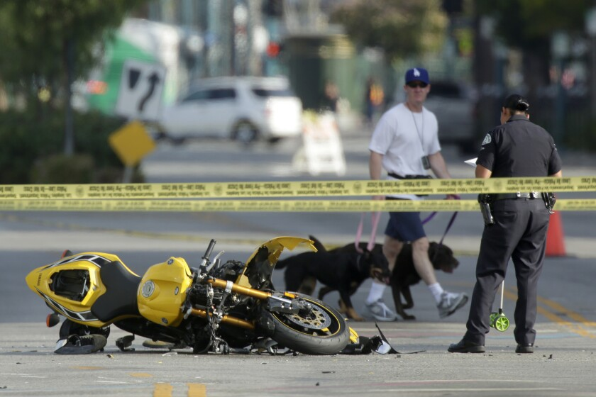 A man walks by with his dogs as an LAPD officer investigates an incident Saturday morning in North Hollywood where a car crashed into a motorcyclist.