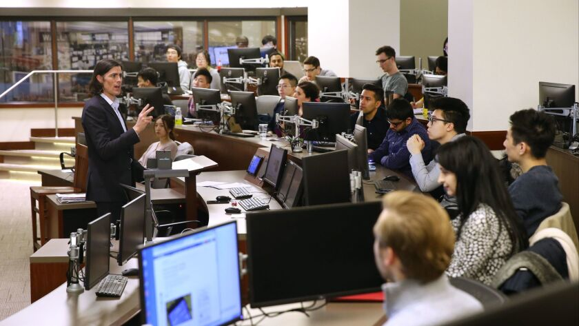 Lamont Black, standing at left, an assistant professor at DePaul University's Driehaus College of Business, incorporates cryptocurrency into his teaching.