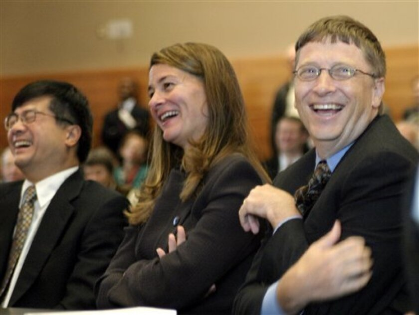 FILE - In this Sept. 12, 2003, file photo Washington Gov. Gary Locke, left, Bill and Melinda Gates, respectively right and center, react to comments by former New York Gov. Mario Cuomo during the grand opening of the William H. Gates Hall, the new home of the University of Washington School of Law,
