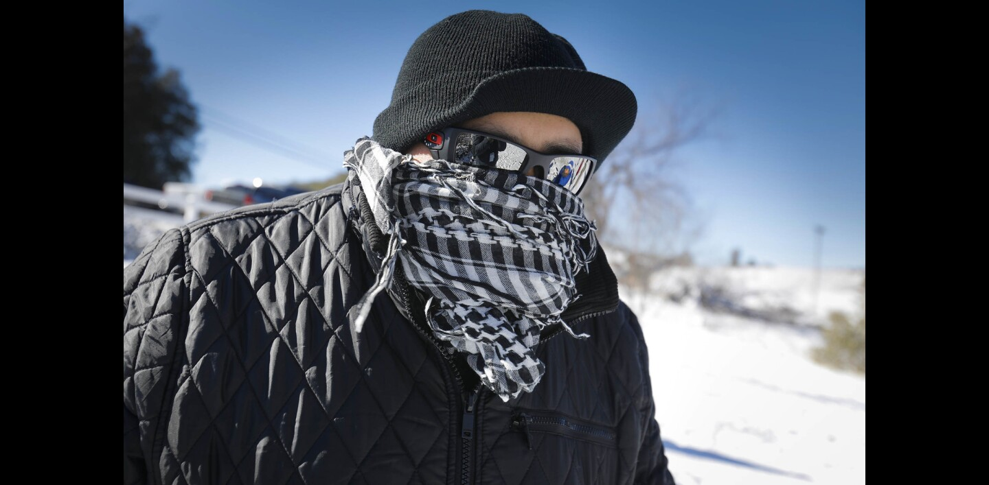 Omar Vega is all bundled up to keep warm while watching his children play in the snow on New Year's Day in Julian, off state Route 79.