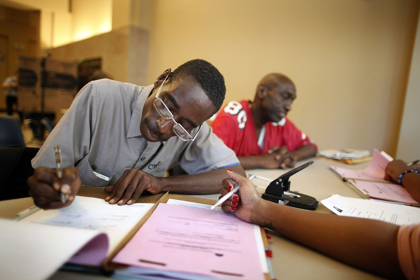 Anthony Smith, 49,fills out paperwork needed to secure his new studio apartment inside the Historic Rosslyn Hotel annex in downtown Los Angeles. Smith is among 75 chronically homeless veterans moving into the $32-million SRO Housing Corp. project.