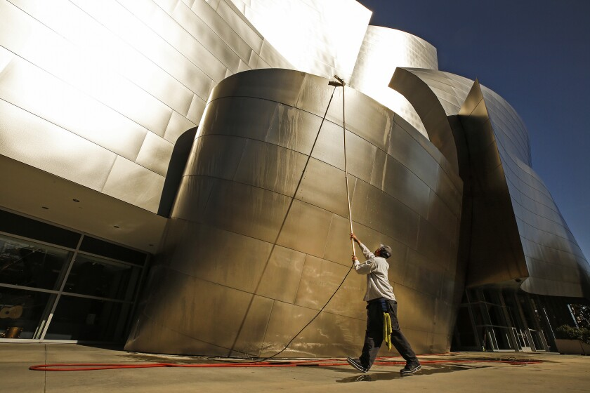 A worker uses a special extension wand to clean the metal exterior of Walt Disney Concert Hall.
