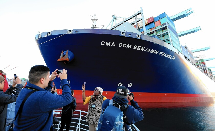 People aboard a passing boat take pictures of the CMA CGM Benjamin Franklin as it unloads cargo at the Port of Los Angeles. The Franklin is the largest container ship to visit a North American port.
