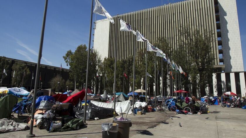 Homeless individuals gather at an encampemnt at the Santa Ana Civic Center near the Orange County Co