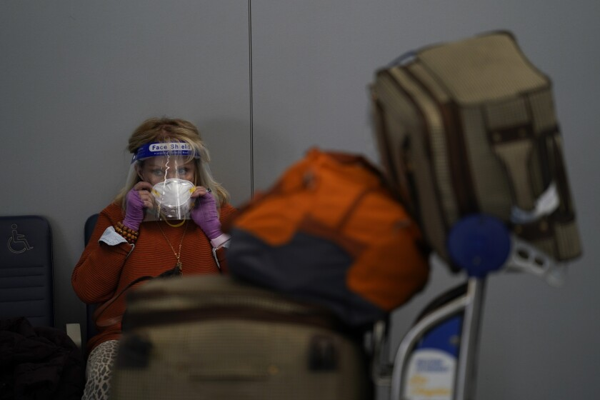 A traveler adjusts her mask while waiting to check in for her flight at the Los Angeles International Airport in Los Angeles, Monday, Nov. 23, 2020. About 1 million Americans a day packed airports and planes over the weekend even as coronavirus deaths surged across the U.S. and public health experts begged people to stay home and avoid big Thanksgiving gatherings. (AP Photo/Jae C. Hong)