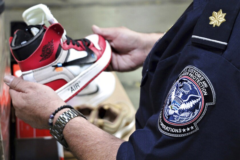 An agent from U.S. Customs and Border Protection holds one of the counterfeit Nike shoes