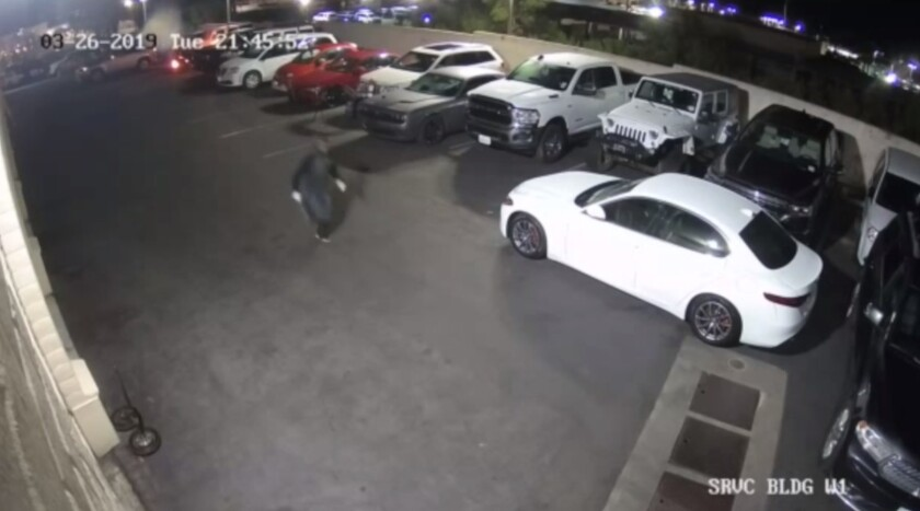 An arson suspect is captured on surveillance footage running away as flames begin to engulf vehicles in the top left corner of the image. The fire destroyed eight vehicles on March 26.