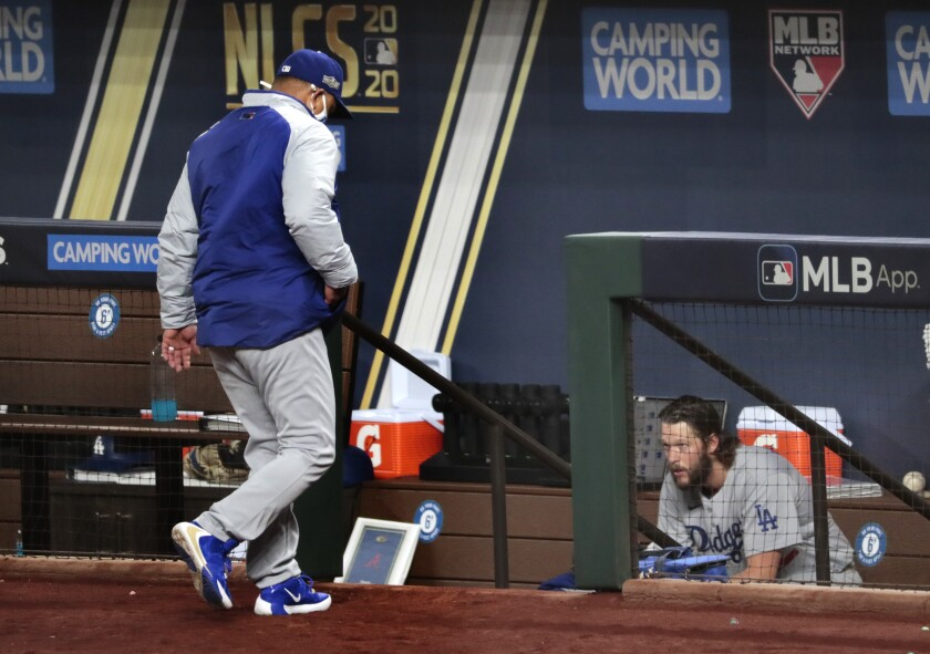 Dodgers manager Dave Roberts returns to the dugout as Clayton Kershaw sits on the bench moments after being pulled.