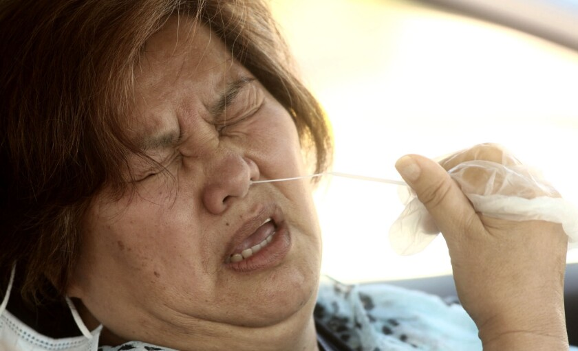 A Carson resident grimaces as she gives herself a coronavirus test with a swab in her nostril while sitting.
