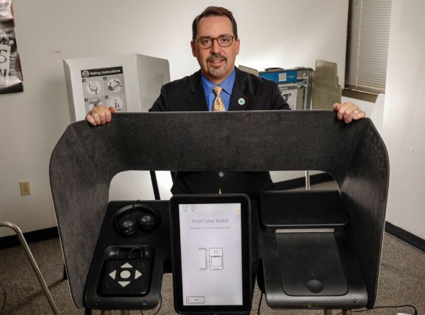 Dean Logan, 52, the registrar-recorder/county clerk for Los Angeles County, stands with a prototype ballot marking device like tho ones that will be introduced during the presidential primary in March.