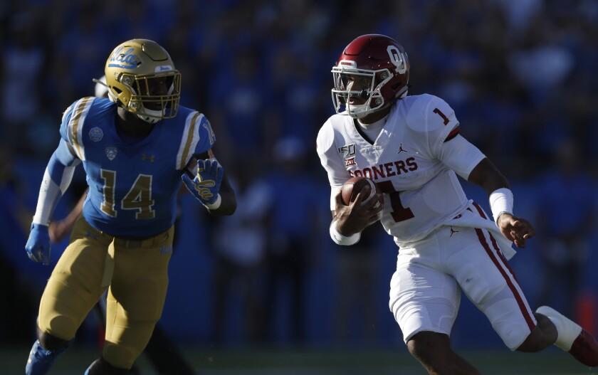 UCLA linebacker Krys Barnes (14) pursues Oklahoma quarterback Jalen Hurts during a game at the Rose Bowl on Sept. 14.