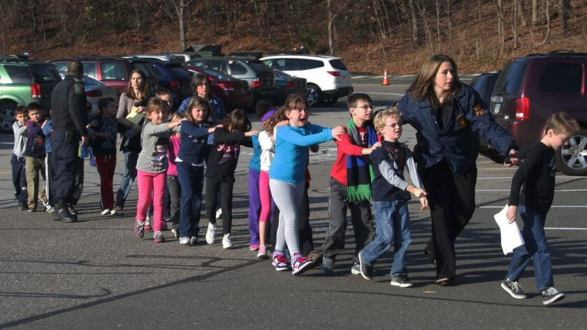 Police lead children from Sandy Hook Elementary School in Newtown, Conn., after the shooting there on Dec. 14, 2012.