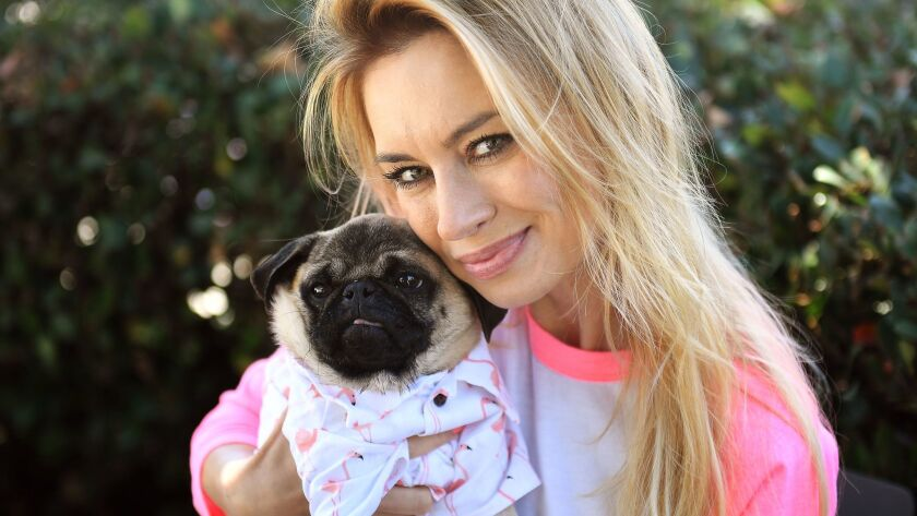 Izabella St. James, known on social media as The Pug Queen, hugs Chance, a pug she rescued from Iran.