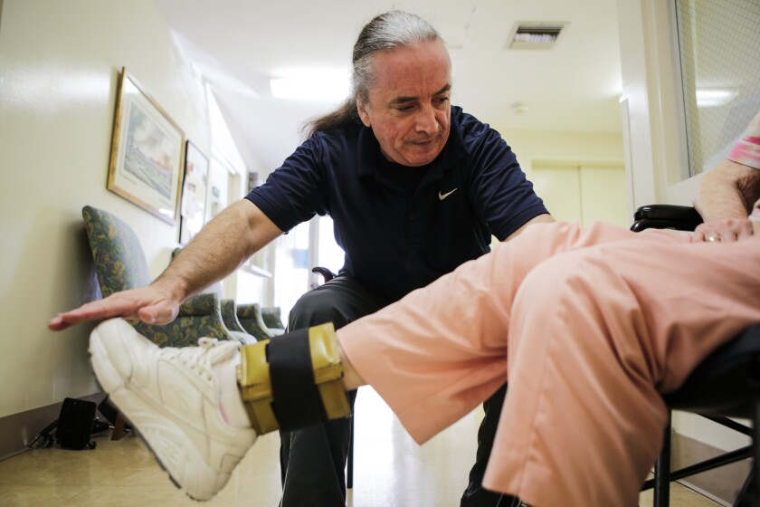 PASADENA, CA -- TUESDAY, JULY 3, 2018-- Andrew Cotham, physical therapist helps a patient with stren