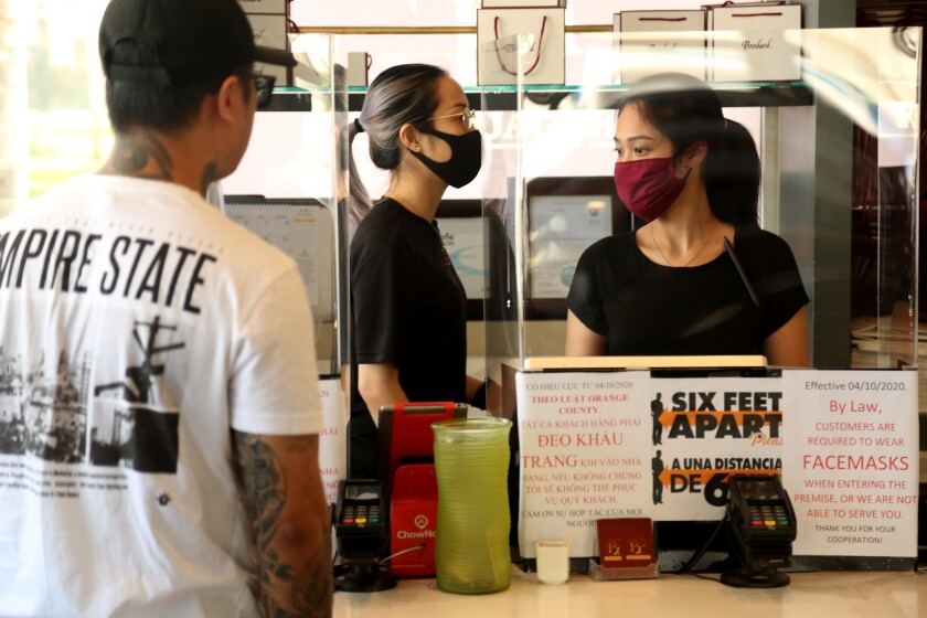 Kayla Le, center, and Nguyen Nguyen, right, both wearing protective masks and gloves, take orders at Brodard Restaurant in Fountain Valley on Monday.