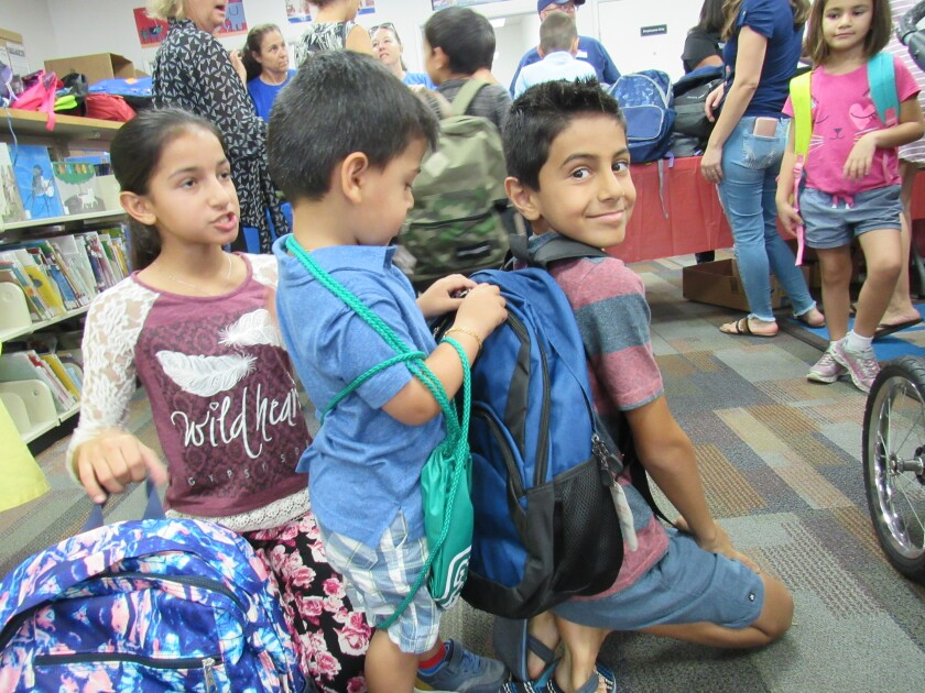 Cajon Park School fifth-grader Matthew Nasser gets his new backpack inspected by brother Nicholas as sister Maria looks on Sunday morning at the Santee branch library. Thousands of kids were given backpacks stuffed with school supplies at the annual event organized by the Santee Mobilehome Owners Action Committee.